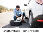 Small photo of Handsome young man lifting the car on the jack for changing flat tire on the road