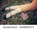girl legs lying on the grass... | Shutterstock . vector #1046805571