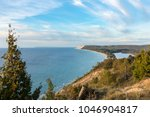 Scenic overlook on the Empire Bluffs Trail overlooks Lake Michigan, Sleeping Bear Dunes National Lakeshore, South Manitou Island, and North Bar Lake, under a blue sky with white clouds.