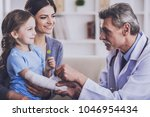 male pediatrician is  checking... | Shutterstock . vector #1046954434