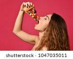 young beautiful woman eat slice ... | Shutterstock . vector #1047035011