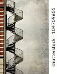 grunge textured picture of a spiral staircase at the edge of an house - stock photo
