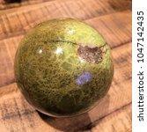 green opal crystal sphere on... | Shutterstock . vector #1047142435