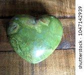 green opal crystal heart on... | Shutterstock . vector #1047142939