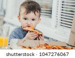 the child in the kitchen eats a ... | Shutterstock . vector #1047276067