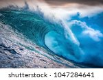 a huge wave crashing at sunset... | Shutterstock . vector #1047284641