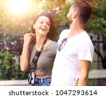 cheerful young couple walking... | Shutterstock . vector #1047293614