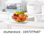fruit basket in bright kitchen | Shutterstock . vector #1047379687