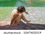 child playing in a pool of... | Shutterstock . vector #1047403519