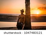 man with straw hat on the beach ... | Shutterstock . vector #1047483121