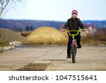 little boy riding his bicycle... | Shutterstock . vector #1047515641