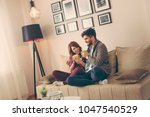 couple sitting on a sofa in the ... | Shutterstock . vector #1047540529
