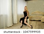 seductive blond sits on chair... | Shutterstock . vector #1047599935