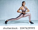 sporty woman doing lunges with...