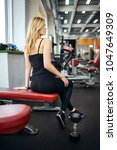 blonde girl sits in the gym.... | Shutterstock . vector #1047649309