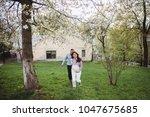 happy couple hold hands running ... | Shutterstock . vector #1047675685