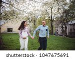 happy couple hold hands running ... | Shutterstock . vector #1047675691