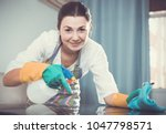 attentive girl cleans table... | Shutterstock . vector #1047798571
