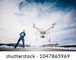 man flying drone in snowy... | Shutterstock . vector #1047865969