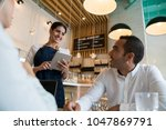 business couple at a bakery... | Shutterstock . vector #1047869791