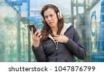 Small photo of jealousy and suspicion in the cell phone, couple problems, adult woman looking at suspicious messages on the phone while on the street listening to music with headphones