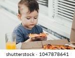 the little boy eats a huge... | Shutterstock . vector #1047878641