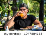 attractive young man eating... | Shutterstock . vector #1047884185
