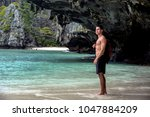 handsome young man standing on... | Shutterstock . vector #1047884209