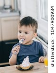 the child in the kitchen eating ... | Shutterstock . vector #1047900934