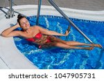 beautiful woman in swimming pool | Shutterstock . vector #1047905731