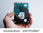 a hand holds hard disk drive... | Shutterstock . vector #1047910867