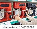 woman shopper selects electric... | Shutterstock . vector #1047953605