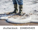 standing in the water at beach... | Shutterstock . vector #1048045405