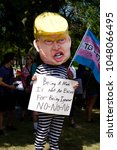 Small photo of DETROIT, MICHIGAN - AUGUST 12, 2017: At the 2017 Slut Walk rally, an activist wears an oversize Trump head and a prison jumpsuit while holding a protest sign
