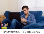 young in the home sofa with... | Shutterstock . vector #1048103737