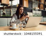 woman at the cafeteria using... | Shutterstock . vector #1048155391