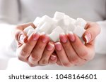 white sugar cubes in woman... | Shutterstock . vector #1048164601