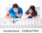 happy young family at baby bed... | Shutterstock . vector #1048167904