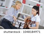 woman learning to play guitar... | Shutterstock . vector #1048184971