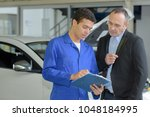 young mechanic showing bill to... | Shutterstock . vector #1048184995