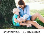 mother with little baby... | Shutterstock . vector #1048218835