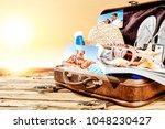 summer suitcase on wooden desk... | Shutterstock . vector #1048230427