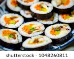 Korean sushi rolls (kimbap or gimbap) cut into small slices and served on a plate. The dish is made from cooked rice and other ingredients rolled up in seaweed sheets or lavers.