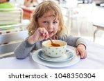 little child eating soup in... | Shutterstock . vector #1048350304