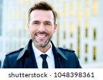 handsome businessman smiling... | Shutterstock . vector #1048398361