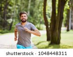 smiling young man running in... | Shutterstock . vector #1048448311