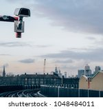 Small photo of CCTV camera with Canary Wharf, London, England, UK in the background - dystopian theme