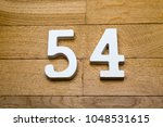 Small photo of Figures fifty-four on a wooden, parquet floor as a background.