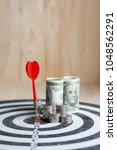 Small photo of Red dart arrow hit the center target of dartboard and money coin metaphor marketing or saving money concept, on wood background