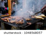 grilling meat with barbecue...   Shutterstock . vector #1048568057